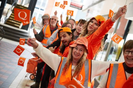 Ornage clad queuers wave flags in shopping arcade